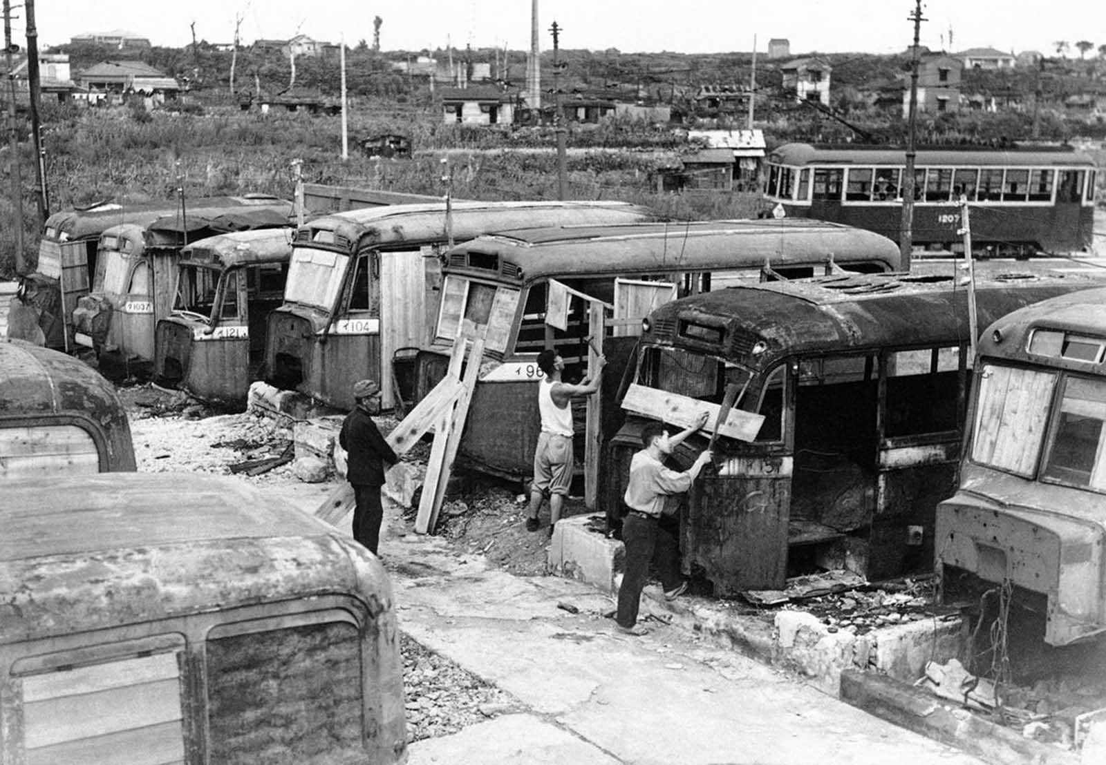 Disabled buses that have littered the streets of Tokyo are used to help relieve the acute housing shortage in the Japanese capital on October 2, 1946. Homeless Japanese who hauled the buses into a vacant lot are converting them into homes for their families.