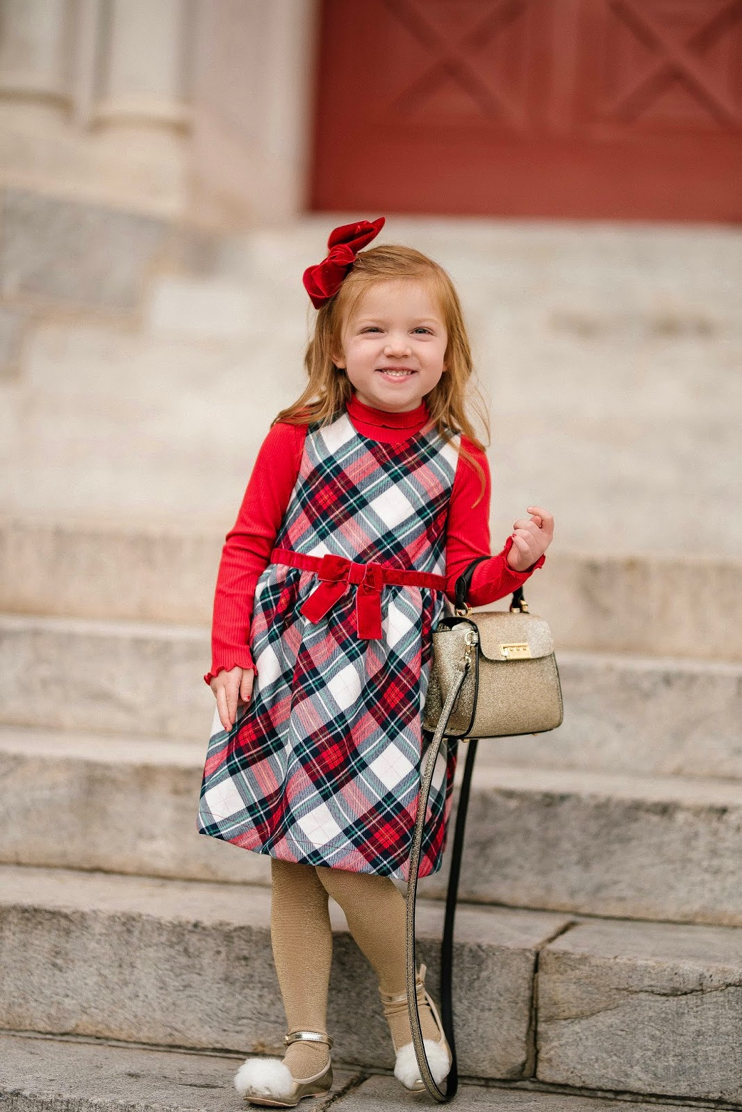 Ready for Christmas in her adorable plaid dress and fuzzy pom pom flats - Something Delightful Blog