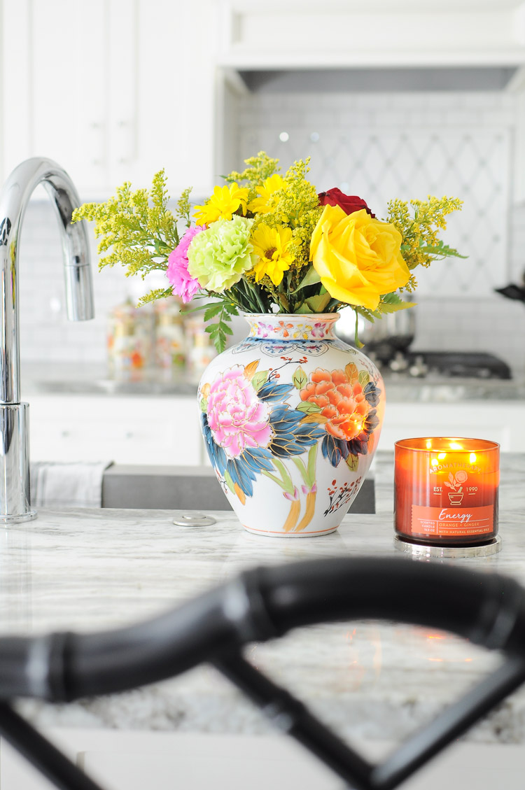 Flowers in a vintage or antique vase add color and personality to this white kitchen island.