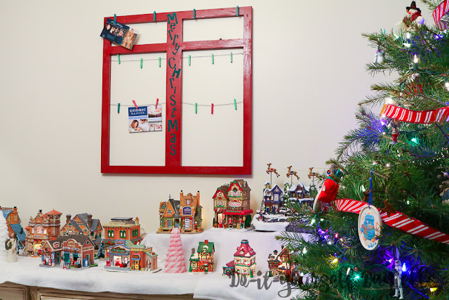 Holiday card display hanging up by the tree and Christmas village.