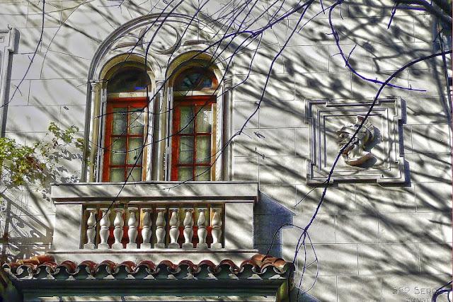 frente de una casa con moldura cabeza guerrero mirando al balcón.