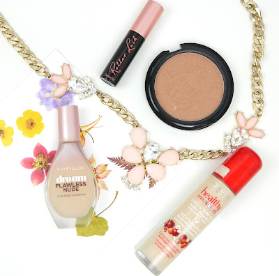 a bottle of bourjois healthy mix foundation with a red cap, maybelline dream flawless foundation with a pink cap, benefit roller lash mascara in a black tube, bronzer in a round pan, and a chunky gold necklace with pink pear shaped stones