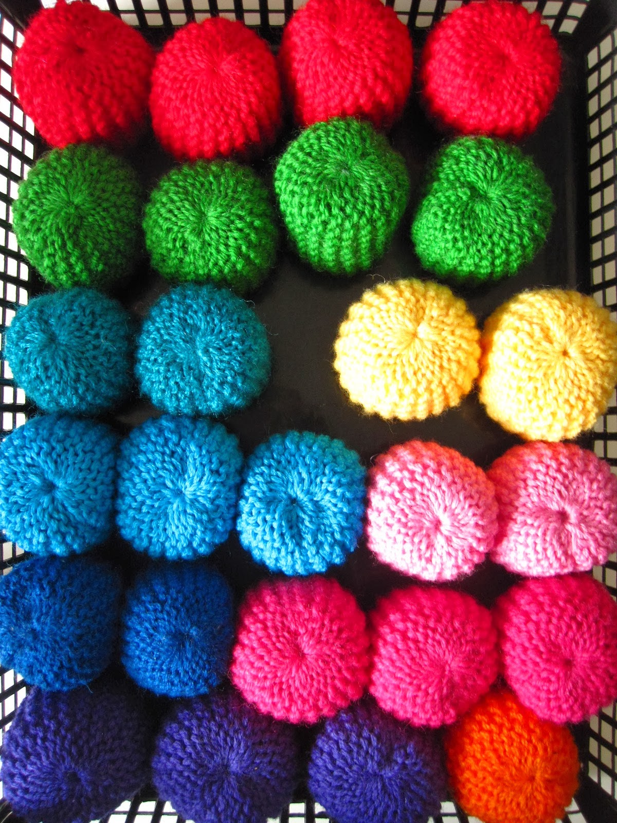 Rows of colourful modern miniature knitted pouffes in a square black plastic basket