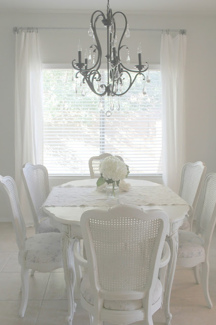 Beautiful serene shabby chic dining room with cane back chairs by Hello Lovely Studio
