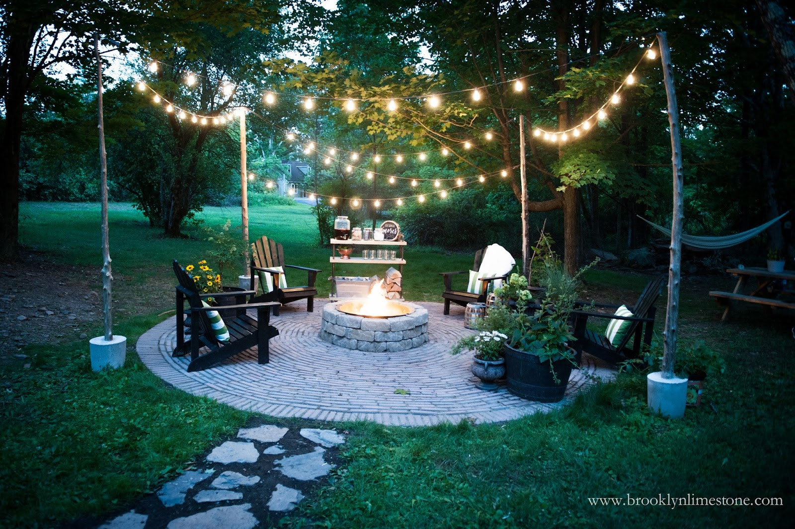 Completed Firepit Patio With Adirondack Chairs Lights And Plants