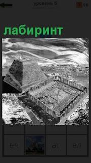 Показана пирамида и рядом лабиринт, огороженный высоким забором в черно белом исполнениии