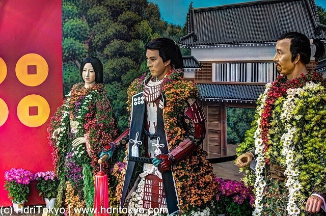 life-size figures which wear clothes made of colorful chrysanthemums.