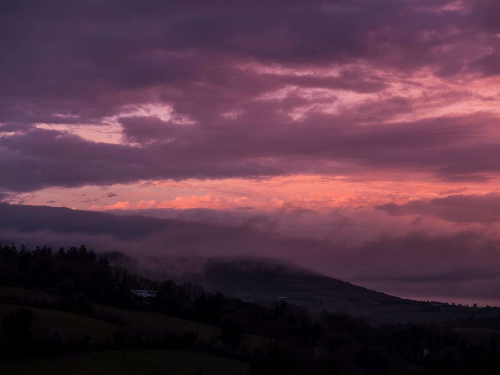Purple and pink sunset clouds over Hilary Mountain in North Cork, Ireland.