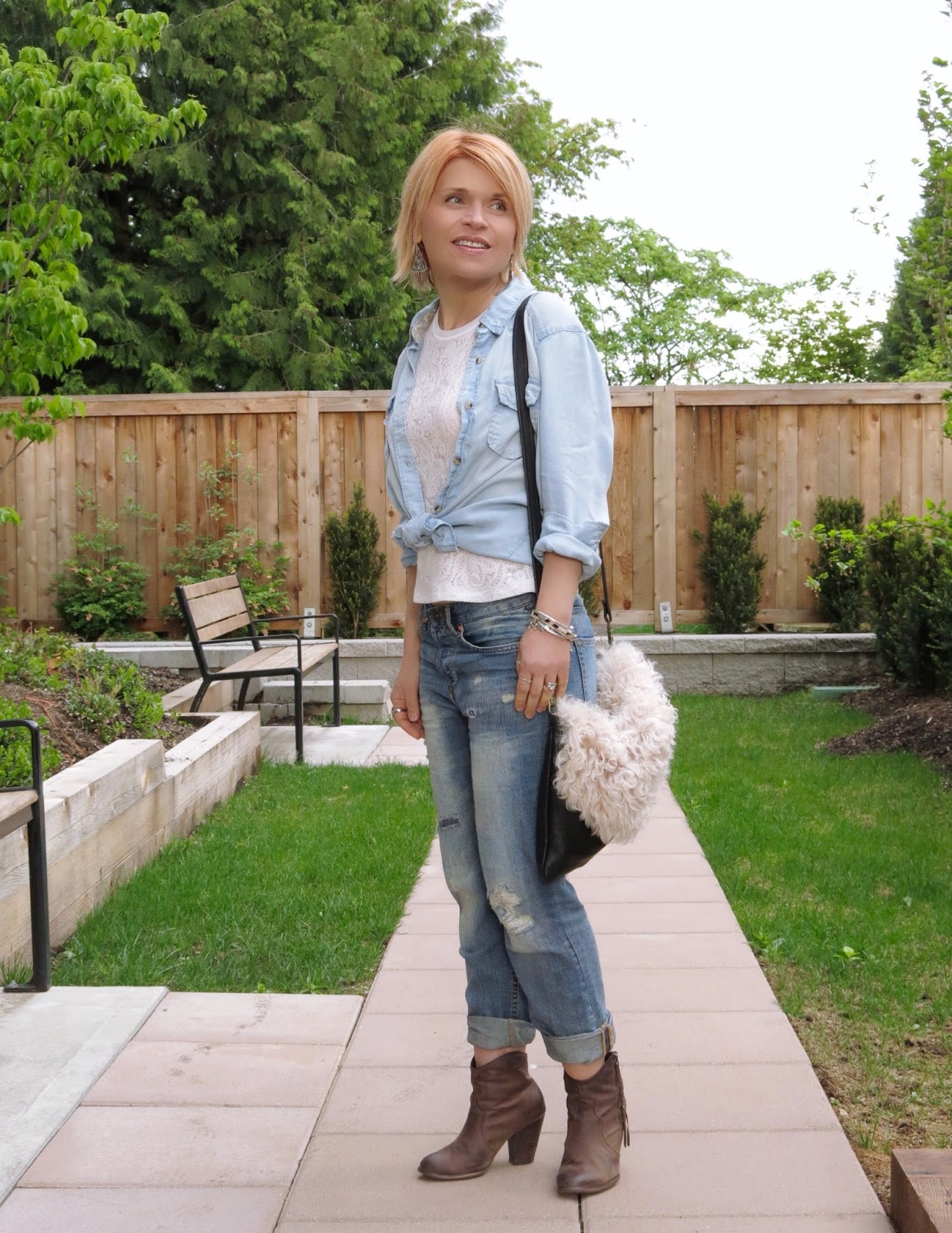 styling boyfriend jeans with a lacy top, chambray shirt, and western-inspired booties