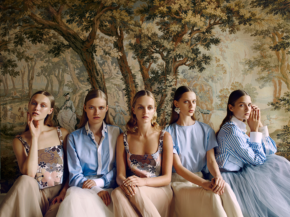 Models seated in front of mural at decaying French Chateau Gudanes
