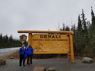 family in front of denali national park sign