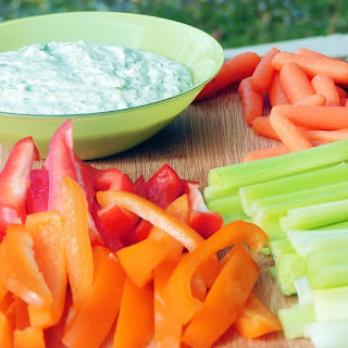 Skinny Green Goddess Dip in a green bowl with vegetables on a wooden board