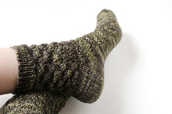 Feet crossed at the ankles wearing dark green hand-knit socks on white background