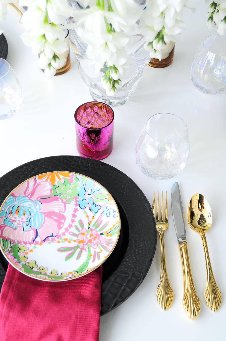 Black plate paired with a Lilly Pulitzer floral dessert plate and gold flatware.