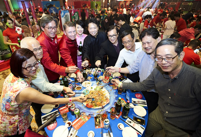 """Lars Lehmann leading the Yee Sang toss at the launching ceremony of """"Prosperity Begins With A POP!"""" with guests."""