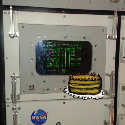 Illusztráció gyerekvershez, háromrétegű torta áll a NASA muzeális űrhajózási számítógépén a Gateway to Space nemzetközi űrkutatási kiállításon.