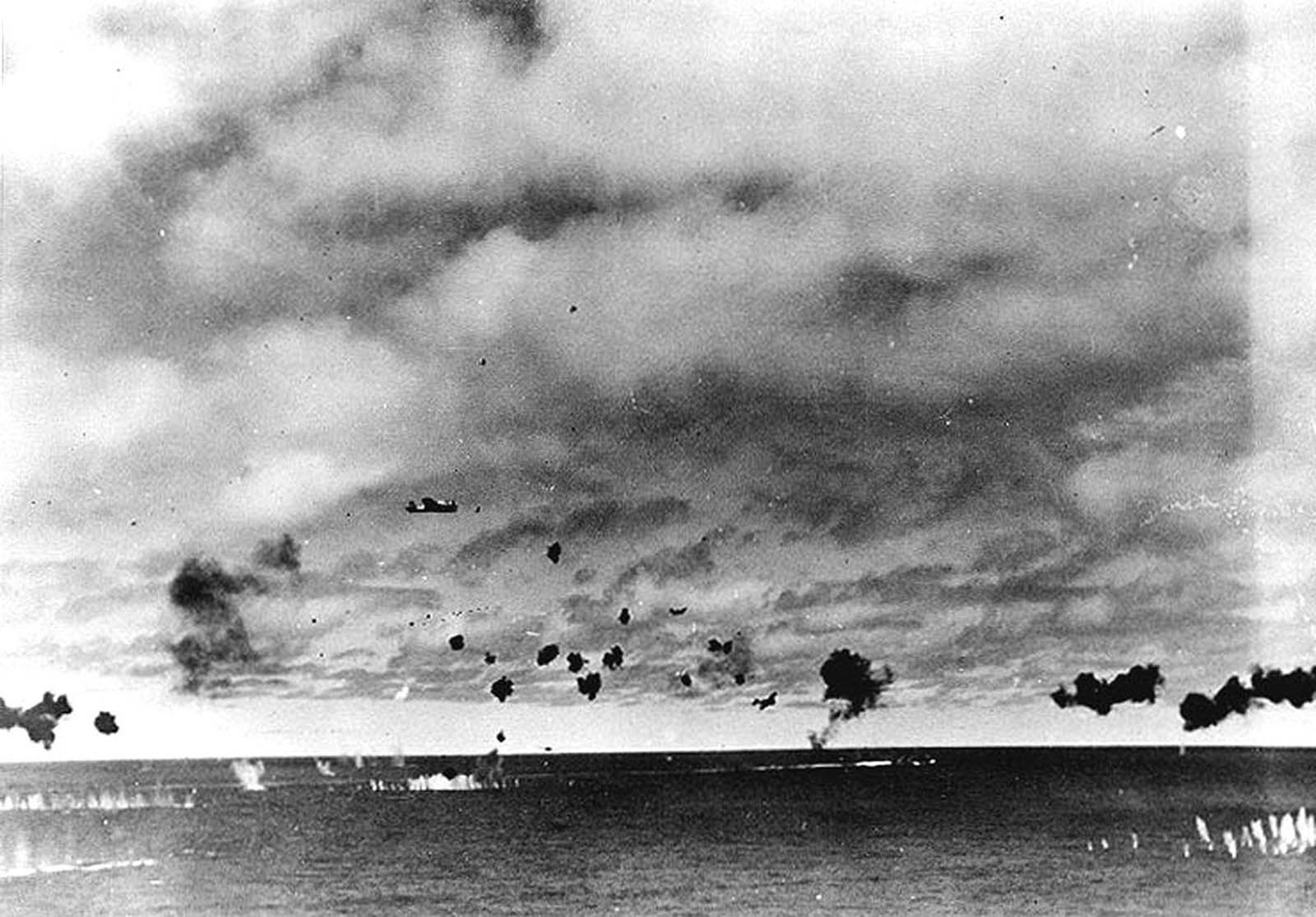 Japanese Type 97 shipboard attack aircraft from the carrier Hiryu amid heavy anti-aircraft fire, during the torpedo attack on USS Yorktown in the mid-afternoon of June 4, 1942. At least three planes are visible, the nearest having already dropped its torpedo. The other two are lower and closer to the center, apparently withdrawing. Smoke on the horizon in right center is from a crashed plane.