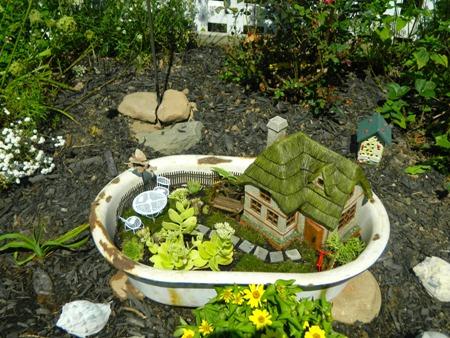 Taman hias mini dalam bak mandi ini boleh dipenuhi oleh tanaman saja, atau boleh ditambahkan figurine untuk membuatnya jadi semacam miniatur rumah