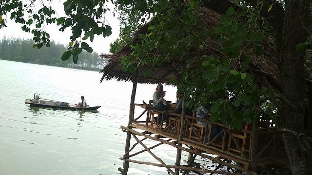 pondokan dan perahu kecil di atas sungai mangrove