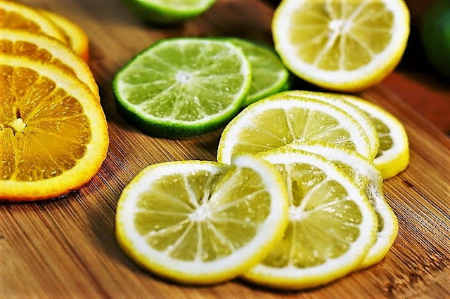 Orange, Lime, Lemon Slices on Cutting Board Image