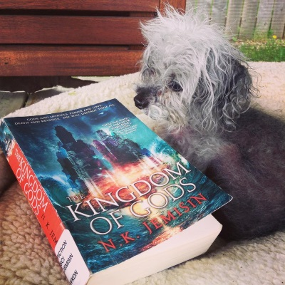 A fuzzy grey poodle, Murchie, lies in a massive beige dog bed in a gazebo. Beside him is a trade paperback copy of The Kingdom of Gods. Its blue-tinged cover features a massive palace hovering slightly above a stormy ocean, seemingly supported by a red burst of magic. An indistinct face hovers behind it.