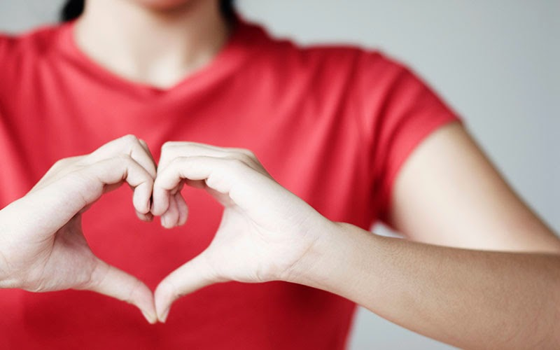 Woman in red making a heart shape with her hands