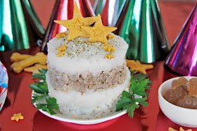Layered meatloaf dog birthday cake with potato frosting topped with star-shaped dog treats