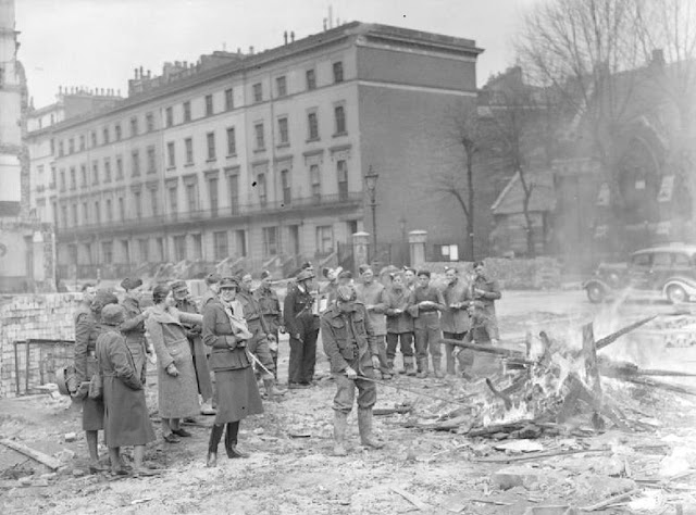 Women of the WW2 - Miss Winifred Ashford, Mrs Pat Macleod and other women of the MTC join men of the Pioneer Corps as they make toast over a fire built of timbers extracted from the rubble of this bomb-damaged area. This photograph was probably taken on Barrie Street, Paddington and the church which is visible behind the group of people is probably St. James's Church. The car which pulls the mobile canteen run by Miss Ashford and Mrs Macleod is parked outside the church.