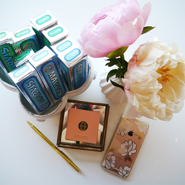 India Rose Cosmeticary flatlay featuring Marvis toothpaste, peonies, gold pen, business cards, rose gold iPhone in floral Sonix case