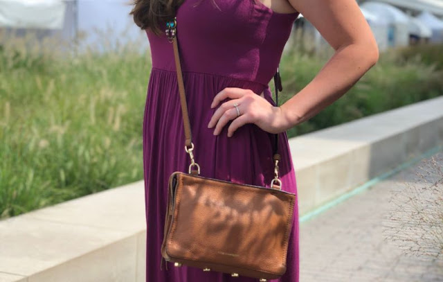 Model is wearing a fuchsia-purple maxi-dress with neutral-colored sandals and accessories.