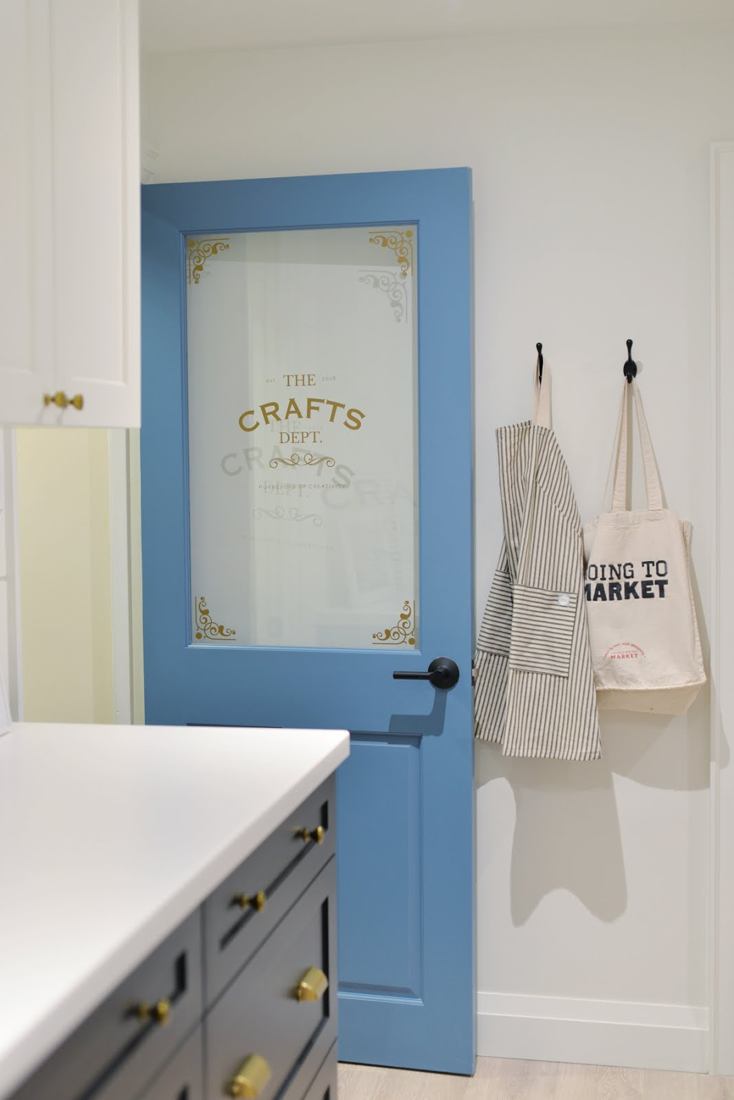 craft room door, blue door, half glass door with decal, striped apron, craft room organization