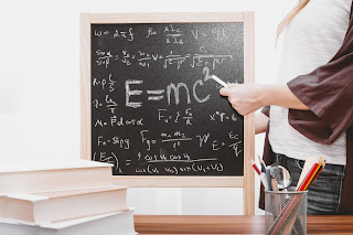 In a classroom, someone is writing on chalkboard, E=mc and other calculations