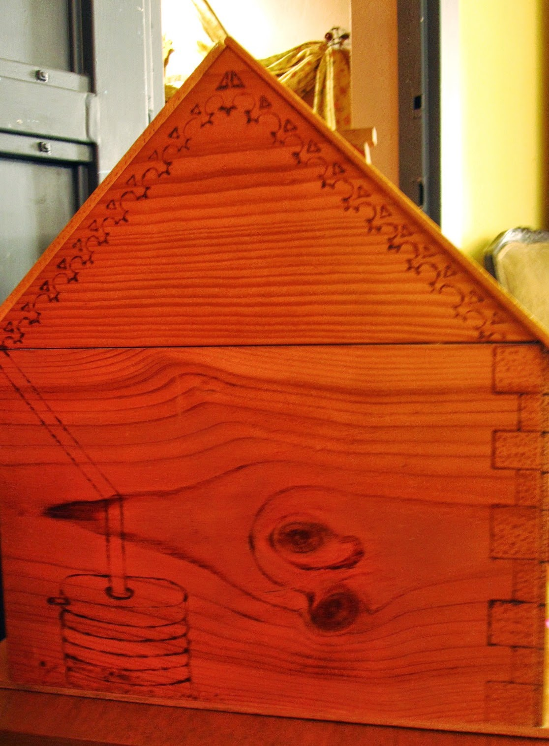 Side of a wooden dolls house, showing pokerwork water barrel and pipe, quoins and iron lace.