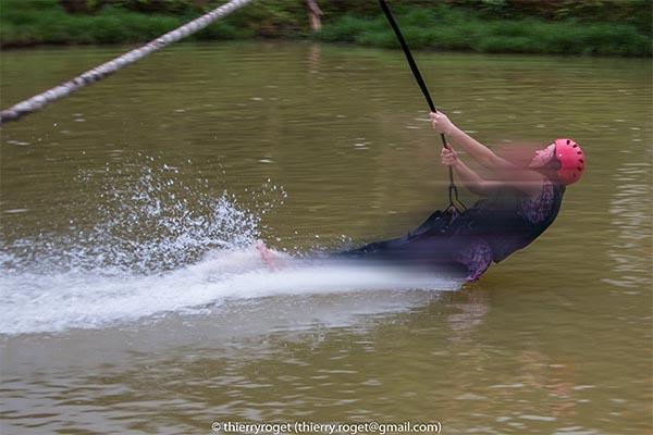 Photo de sport : descente à la tyrolienne et atterrisage dans l'eau (ajout de flou)