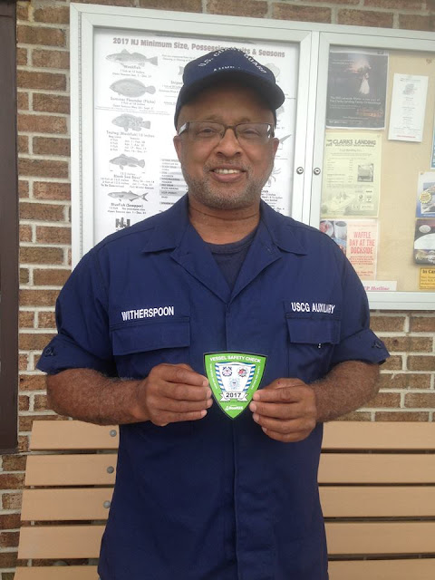 David Witherspoon poses with vessel safety sticker awarded to those who pass the vessel inspection.