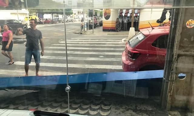 Forte ventania faz placa de loja cair e atingir veículo, em Patos