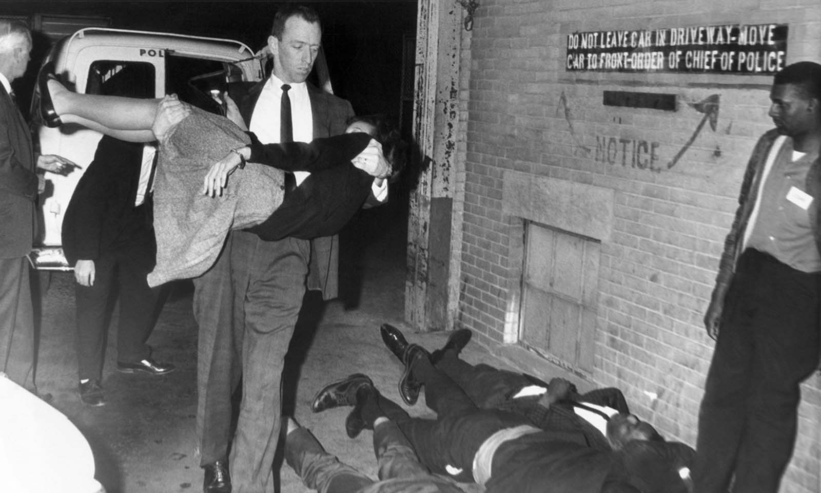 A police officer carrying a young girl walks past three civil rights demonstrators on the ground next to the Tulsa, Oklahoma, police station on April 2, 1964. The demonstrators were part of 54 arrested at a Tulsa restaurant. Members of the group, backed by the Congress of Racial Equality, went limp when arrested and forced officers to carry them from the restaurant and the paddy wagon.