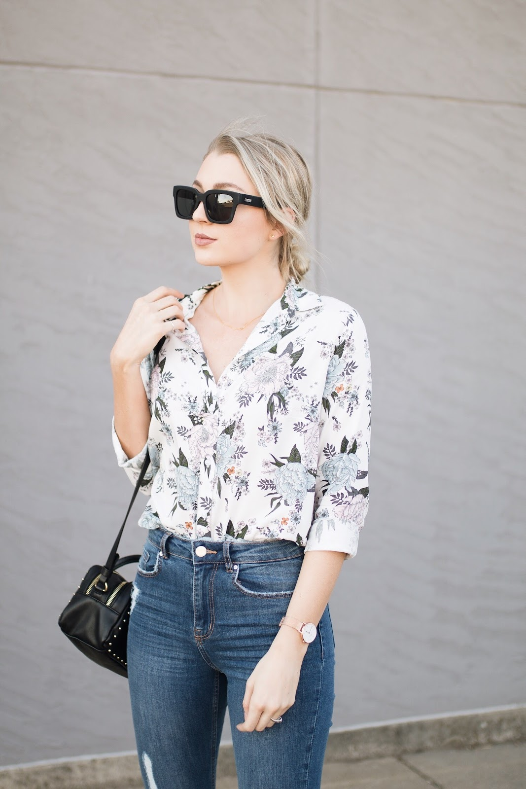 floral blouse tucked into high-waisted jeans