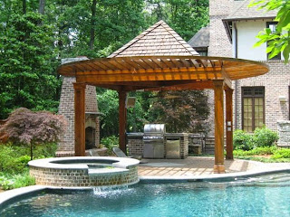 adorable backyard design with bricks hot tub above pool near outdoor kitchen patio with pergola and pyramid tile roofing