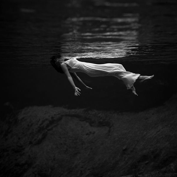 "Underwater view of a woman, wearing a long gown, floating in water. Photograph by Toni Frissell at Weeki Wachee Springs, Florida (1947). This image was later used as the cover for the album Undercurrent by Bill Evans and Jim Hall, the album Tears in Rain by This Ascension and Osvaldo Golijov's ""Oceana,"" and also for the album Whispering Sin by the Beauvilles."