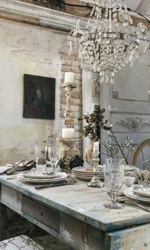 Distressed #farmtable and stone walls in a #Frenchfarmhouse dining room with crystal chandelier