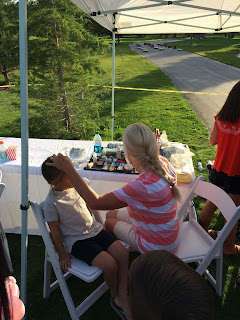 A young girl getting her face painted by a professional face painter
