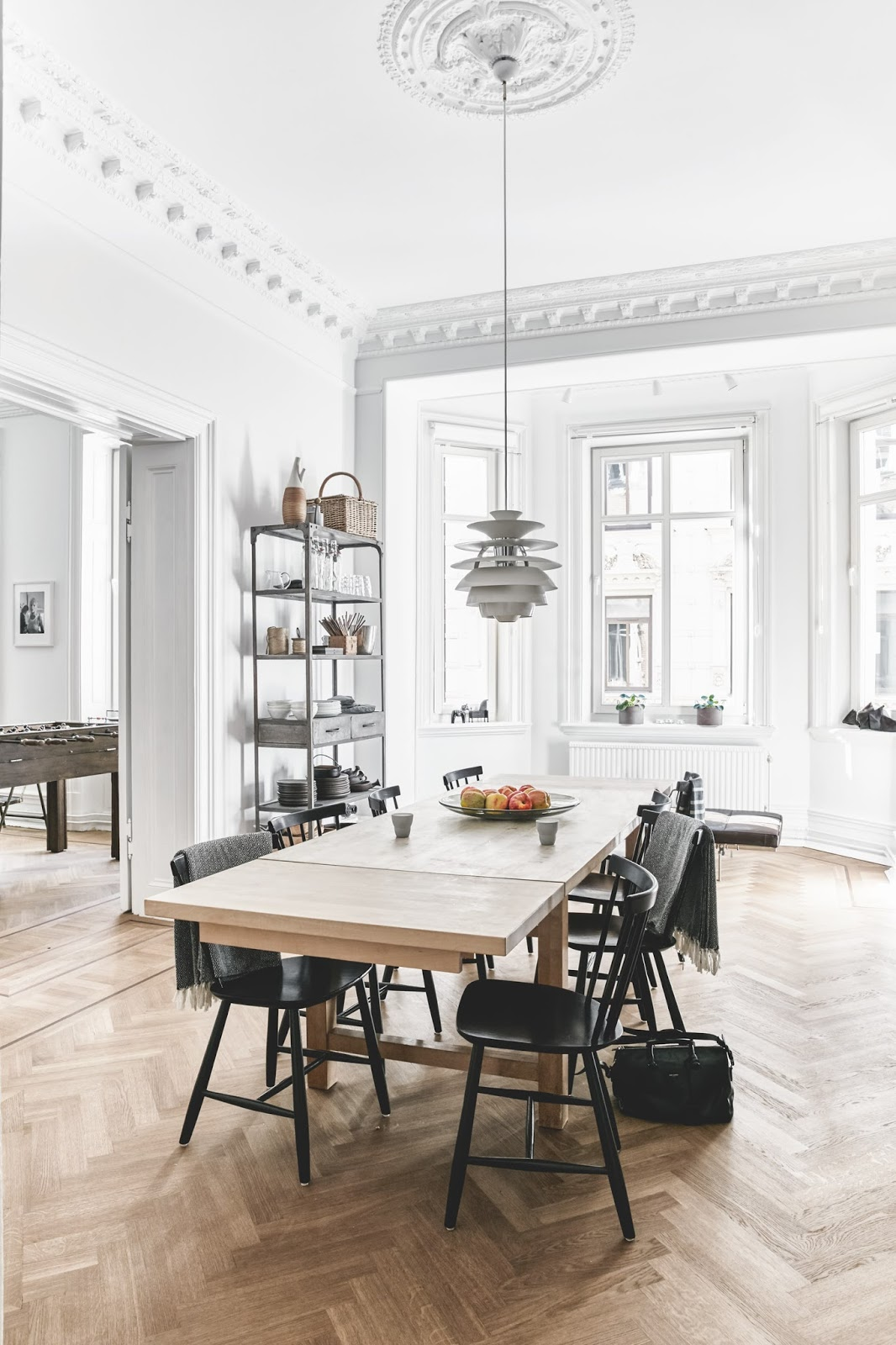poul henningsens snowball lamp and large dining table inside of an large scandinavian apartment