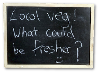 A blackboard sign saying 'Local veg, what could be fresher?'