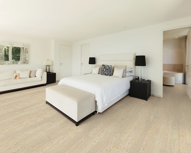 Light grey wood flooring adds an element of style to this bedroom.