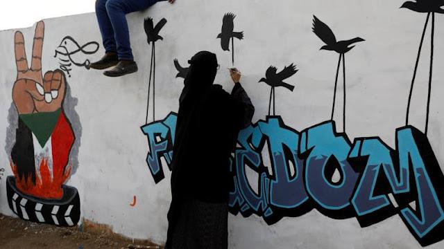 فتاة ترسم جدارية الثورة في السودان
