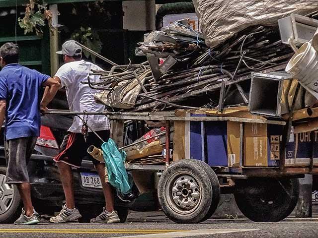 Dos cartoneros tirando un carro cargado por Buenos Aires
