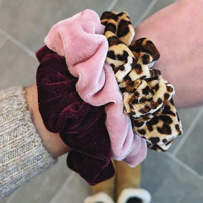 3 velvet scrunchies on wrist with tile background