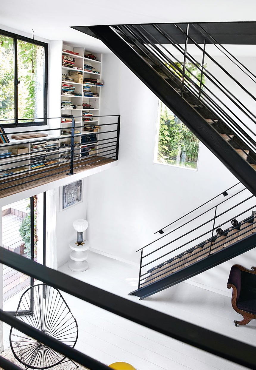 luxury large family villa with mid century modern design and large bookcase, staircase, white floor
