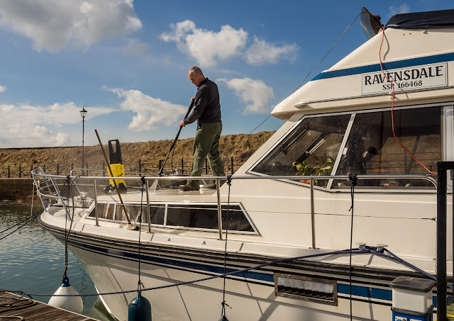 Photo of Phil pressure-washing Ravensdale's foredeck